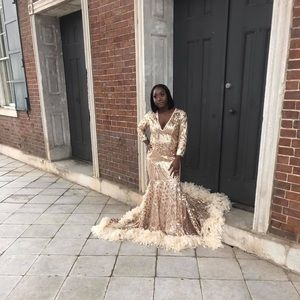 gold designed prom dress with feathers at the end